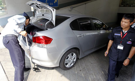 Thai security guards check a car at the entrance of the Israeli embassy building in central Bangkok